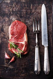 Raw fresh meat Ribeye Steak. Rosemary and vintage fork and knife carving set on dark background Royalty Free Stock Photography