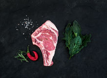 Raw fresh meat ribeye steak with salt, chili pepper, rosemary and spinach over black slate stone background. Top view Stock Image