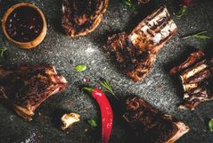 Grilled lamb or beef ribs. Raw fresh meat, roasted or grilled lamb or beef ribs with red tomato sauce, hot pepper, garlic and spices on dark stone background stock images