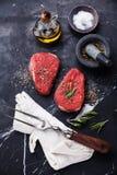 Raw fresh meat rump Steak. Seasoning and meat fork on dark marble background Royalty Free Stock Photo