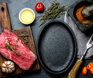 Raw fresh meat steak beef tenderloin, herbs and spices around frying pan plate. Food cooking ackground with copy space.  stock photos