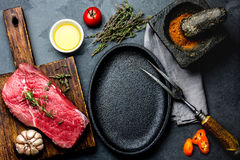 Raw fresh meat steak beef tenderloin, herbs and spices around frying pan plate. Food cooking ackground with copy space.  royalty free stock photo