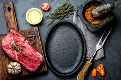 Raw fresh meat steak beef tenderloin, herbs and spices around frying pan plate. Food cooking ackground with copy space.  royalty free stock image