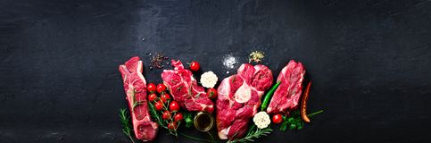 Raw fresh meat steak with cherry tomatoes, hot pepper, garlic, oil and herbs on dark stone, concrete background. Banner. stock photo
