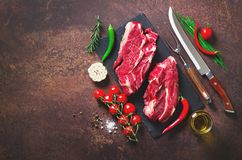 Raw fresh meat steak with cherry tomatoes, hot pepper, garlic, oil and herbs on dark stone, concrete background. Banner. royalty free stock photography