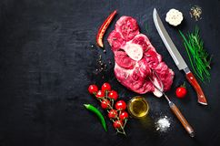 Raw fresh meat steak with cherry tomatoes, hot pepper, garlic, oil and herbs on dark stone, concrete background. Banner. stock images