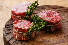 Raw fresh meat Steak filet mignon and thyme. Raw fresh marbled meat Steak filet mignon and thyme on wooden background Royalty Free Stock Photography