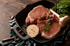 Raw fresh meat steak on grill iron pan, seasoning and Meat fork on wooden background stock images