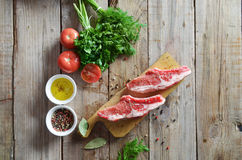 Raw fresh meat. Steak with salt and pepper on cutting board on dark wooden background Royalty Free Stock Photography