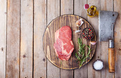 Raw fresh meat Steak with salt and pepper, rosemary and tomatoes on cutting board Copy space. Top view. Raw fresh meat Steak with salt and pepper, rosemary and Royalty Free Stock Image