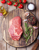 Raw fresh meat Steak with salt and pepper, rosemary and tomatoes on cutting board on dark wooden background Top view Stock Image