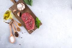 Raw fresh meat steak and seasoning spices  on a gray concrete background. Top view. Copy space Stock Photography