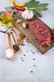 Raw fresh meat steak and seasoning spices  on a gray concrete background Top view. Copy space Stock Image