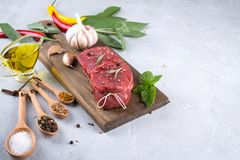 Raw fresh meat steak and seasoning spices  on a gray concrete background Top view. Copy space Royalty Free Stock Images
