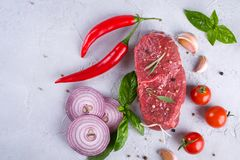 Raw fresh meat steak and seasoning spices  on a gray concrete background Top view. Copy space Stock Images