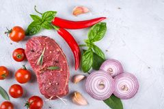 Raw fresh meat steak and seasoning spices  on a gray concrete background Top view. Copy space Stock Photo