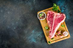 Raw t-bone steak. Raw fresh meat, t-bone beef steak with spices and herbs on cutting board, concrete table top view copy space stock photography
