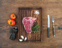 Raw fresh meat t-bone steak with garlic cloves, tomatoes, rosemary, pepper and salt on serving board over rustic wooden Royalty Free Stock Photography