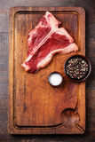 Raw fresh meat T-Bone Steak. With salt and pepper on cutting board on dark wooden background Stock Photography