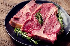 Raw fresh meat t-bone steak and seasoning on wooden background Royalty Free Stock Images