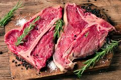 Raw fresh meat t-bone steak and seasoning on wooden background Royalty Free Stock Photos