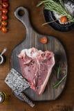 Raw fresh meat T-bone steak. On wooden cutting board Stock Photos