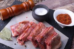 Raw fresh meat, uncooked lamb or beef ribs with pepper, garlic, salt, bay leaves and spices on dark stone background. Ready for cooking. copy space Royalty Free Stock Photos
