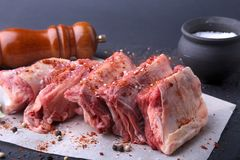 Raw fresh meat, uncooked lamb or beef ribs with pepper, garlic, salt, bay leaves and spices on dark stone background. Ready for cooking. copy space Royalty Free Stock Photo