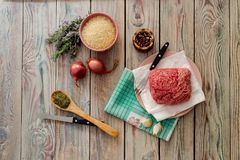Raw, fresh minced meat on a plate, spices, rice and vegetables. Cooking food. Raw, fresh minced meat on a plate, spices, rice and vegetables on a wooden table Stock Photography