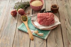 Raw, fresh minced meat on a plate, spices, rice and vegetables. Cooking food. Raw, fresh minced meat on a plate, spices, rice and vegetables on a wooden table Royalty Free Stock Images