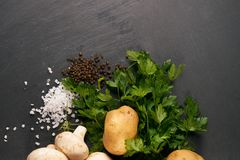 Raw fresh onions, potatoes, garlic, mushroom. Greens and seasoning on dark stone background with copy space. Top view ingredients for cooking a delicious cream Royalty Free Stock Image
