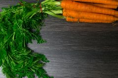 raw organic carrot bunch on black table Royalty Free Stock Photos