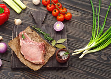 Raw fresh piece of meat on the bone with vegetables Royalty Free Stock Image