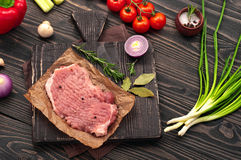 Raw fresh piece of meat with vegetables. On a dark rustic background. top view with copy space Royalty Free Stock Image