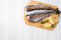 Raw fresh Pollock fish on a wooden Board with lemon Copy space. Raw fresh Pollock fish on a wooden Board with lemon. Copy space royalty free stock photo
