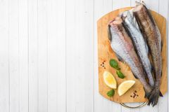 Raw fresh Pollock fish on a wooden Board with lemon Copy space. Raw fresh Pollock fish on a wooden Board with lemon. Copy space stock images