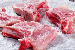 Raw fresh pork chops on a white parchment paper, top view Royalty Free Stock Image