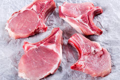 Raw fresh pork chops on a white parchment paper, top view. Raw fresh pork chops on a white parchment paper on an old rustic table, top view Royalty Free Stock Images