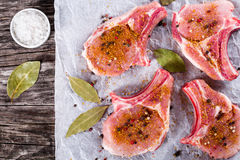 Raw fresh pork chops on a white parchment paper, top view Royalty Free Stock Photos