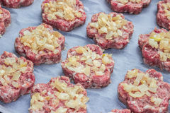 Raw fresh pork cutlets with fried onions in the shape of a flower on parchment paper.  Stock Photography