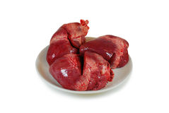 Raw fresh pork hearts on a dish isolated against white background. Raw fresh pork heart isolated against white background Royalty Free Stock Image