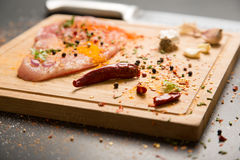 Raw fresh pork meat on board with condiments on dark background Stock Images