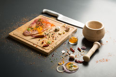 Raw fresh pork meat on board with condiments on dark background Stock Photo