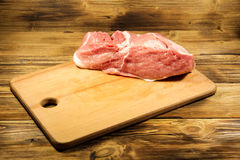 Raw fresh pork meat on cutting board on wooden table. Raw fresh pork meat on cutting board on the wooden table Royalty Free Stock Photo