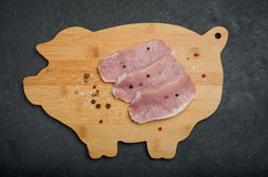 Raw fresh pork meat on wooden board on black background. Top view, horizontal Royalty Free Stock Images