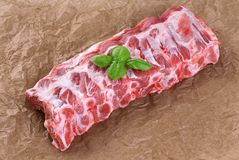 Raw fresh pork ribs and basil on the background of craft paper. Top view Stock Photography