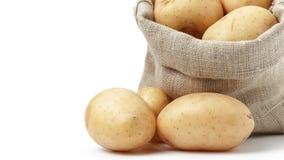 Raw fresh potatoes in burlap bag white copy space Royalty Free Stock Photos