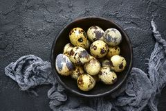 Raw fresh quail eggs.Top view with copy space. Raw fresh quail eggs in a bowl over black slate, stone or concrete background.Top view with copy space Stock Images