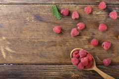 Fresh raspberries in a spoon. Raw fresh raspberries in a spoon on a wooden background, well visible texture of berries, space for text Stock Image