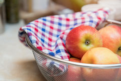 Raw fresh red apple with checkered napkin in sieve Stock Image